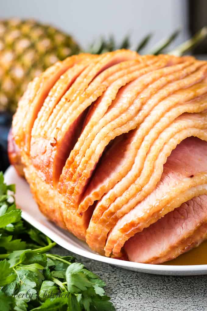 A bone-in oven baked ham on a plate.