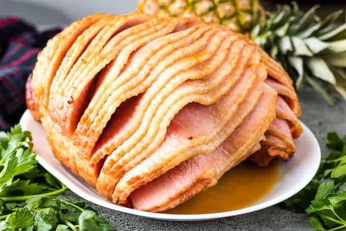 Spiral cut ham with a brown sugar glaze on a platter.