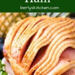 The glazed ham on a platter with parsley.