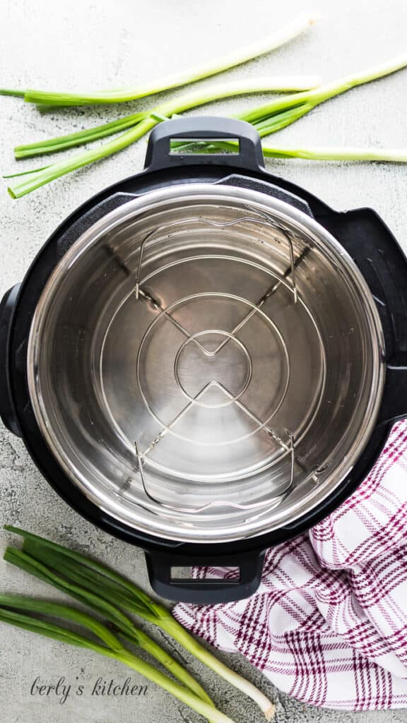 A pressure cooker with liner, trivet, and water added.