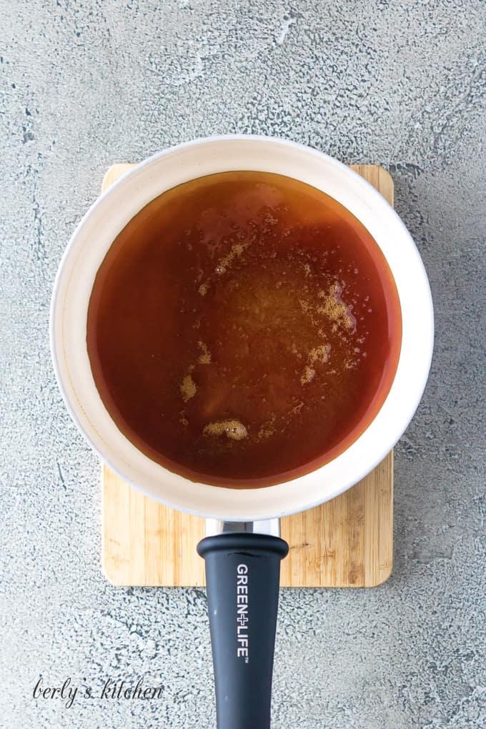 The caramel sauce cooking in a medium saucepan.