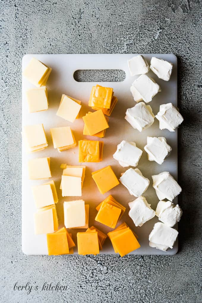 The cheeses cut into small squares on a cutting board.