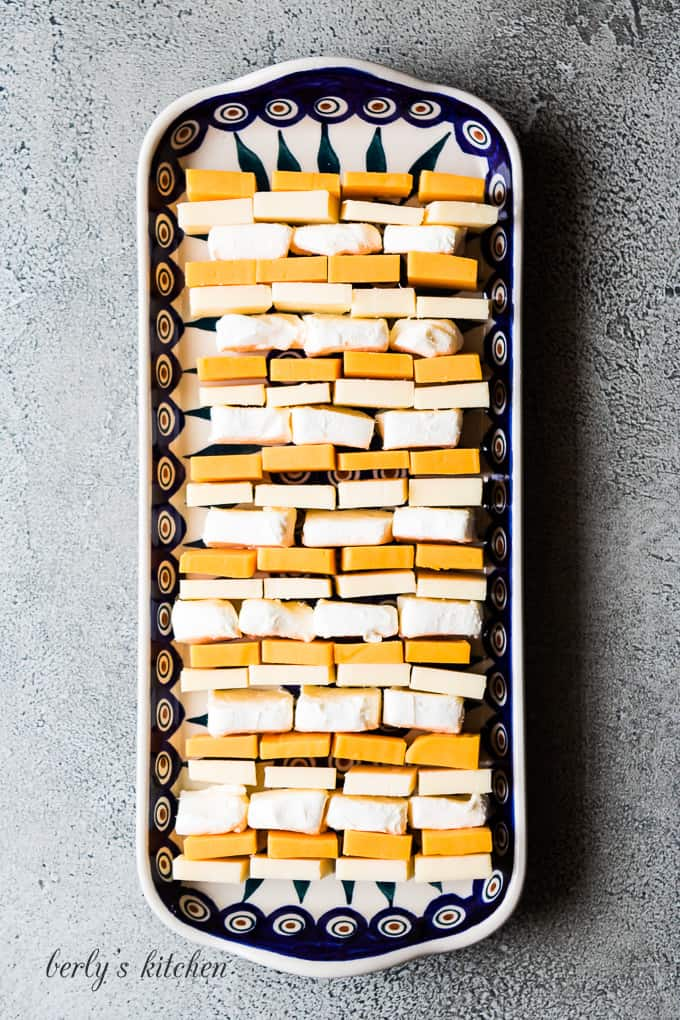 The cheese squares arranged on a platter with tall rim.