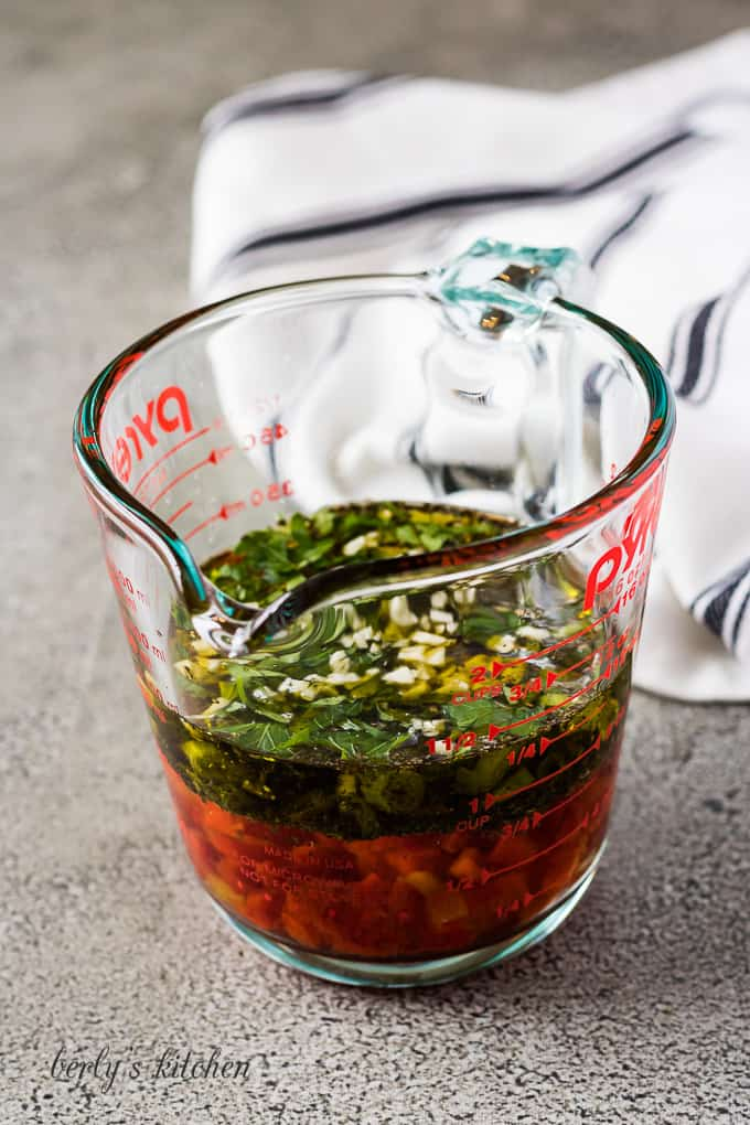 Vinegar, oil, and other ingredients in a glass measuring cup.