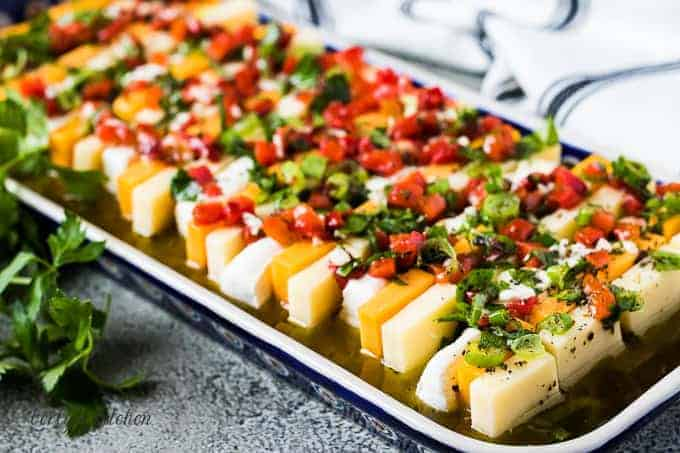The finished marinated cheese served on a colorful rectangular plate.