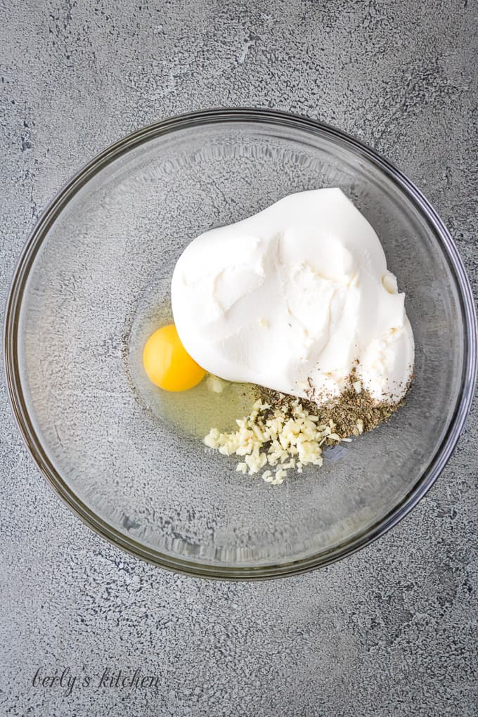 Ricotta cheese and other ingredients in a large mixing bowl.