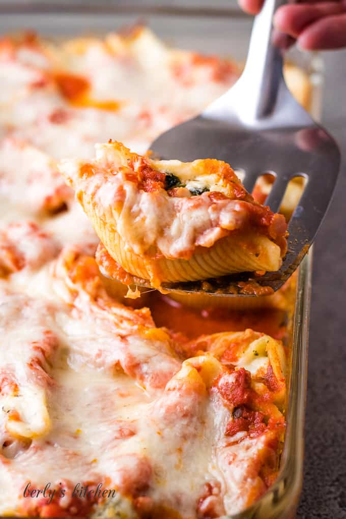 One cheesy pasta shell being lifted from the baking dish.