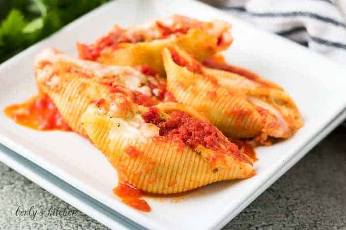 Four ricotta stuffed pasta shells on a decorative square plate.