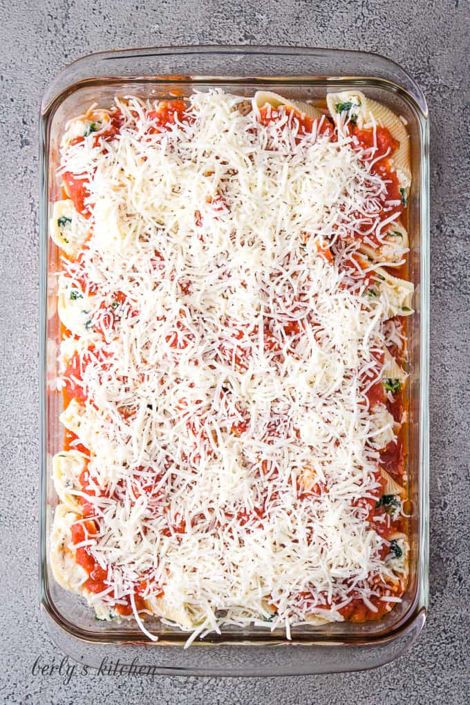 Marinara sauce and mozzarella placed over the stuffed pasta shells.