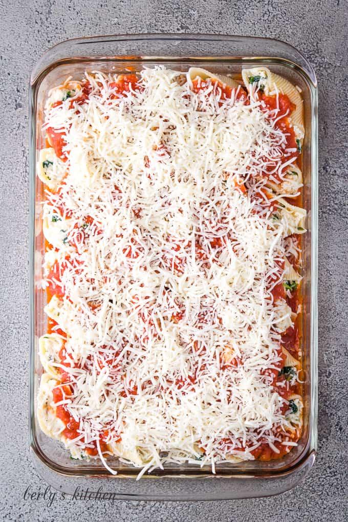 Marinara sauce and mozzarella placed over the stuffed pasta shells.