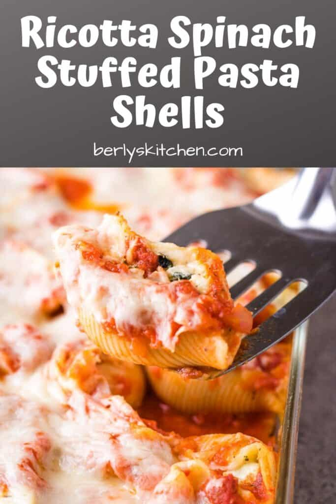 A ricotta spinach stuffed pasta shell being lifted from the pan.
