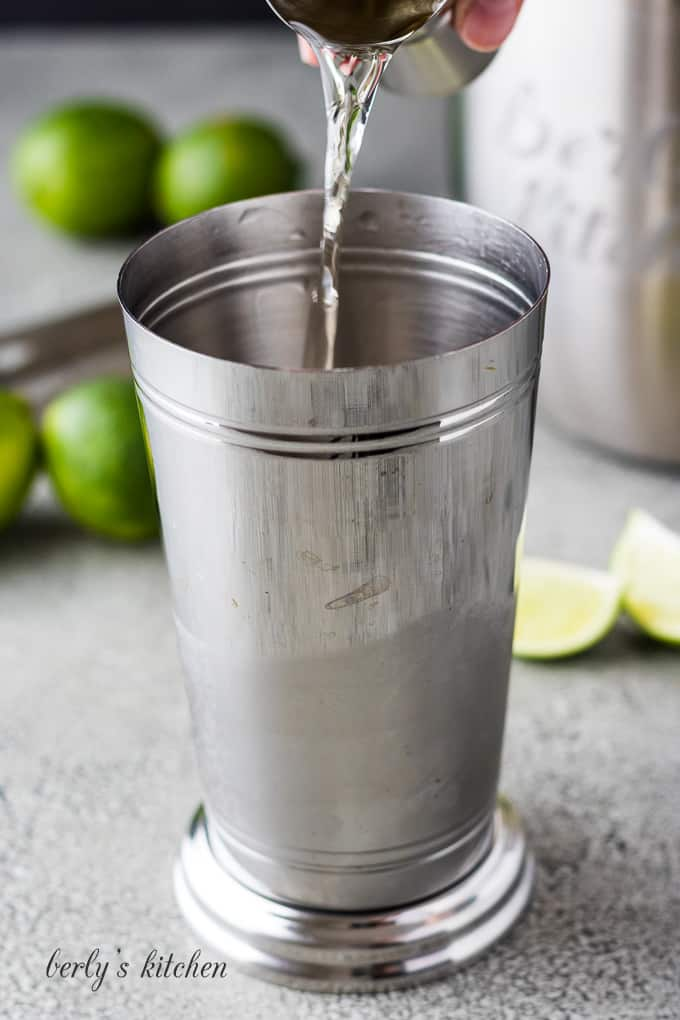 A shot of tequila being added to a cocktail shaker.