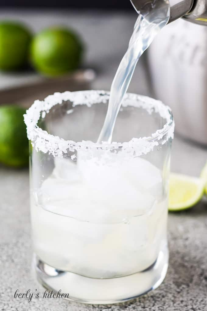 The margarita being poured into the cocktail glass with ice.