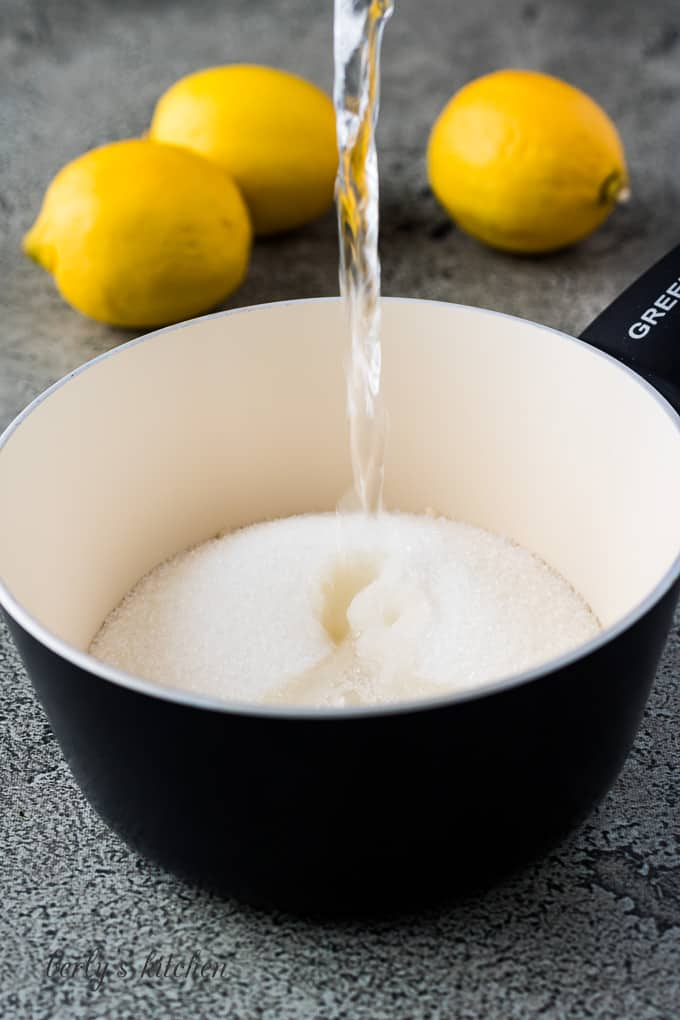 A cup of water pouring into a saucepan with sugar.