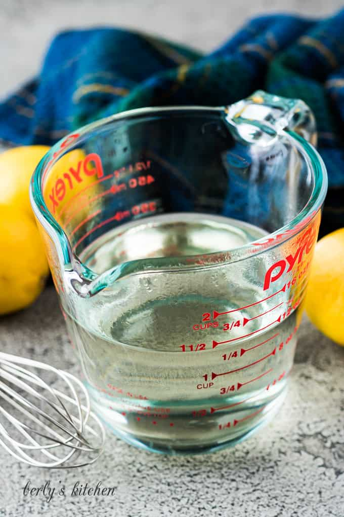 The syrup in a measuring cup surrounded by fresh lemons.