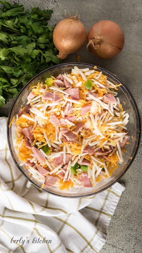Hash browns, cheese, peppers and other ingredients in a bowl.