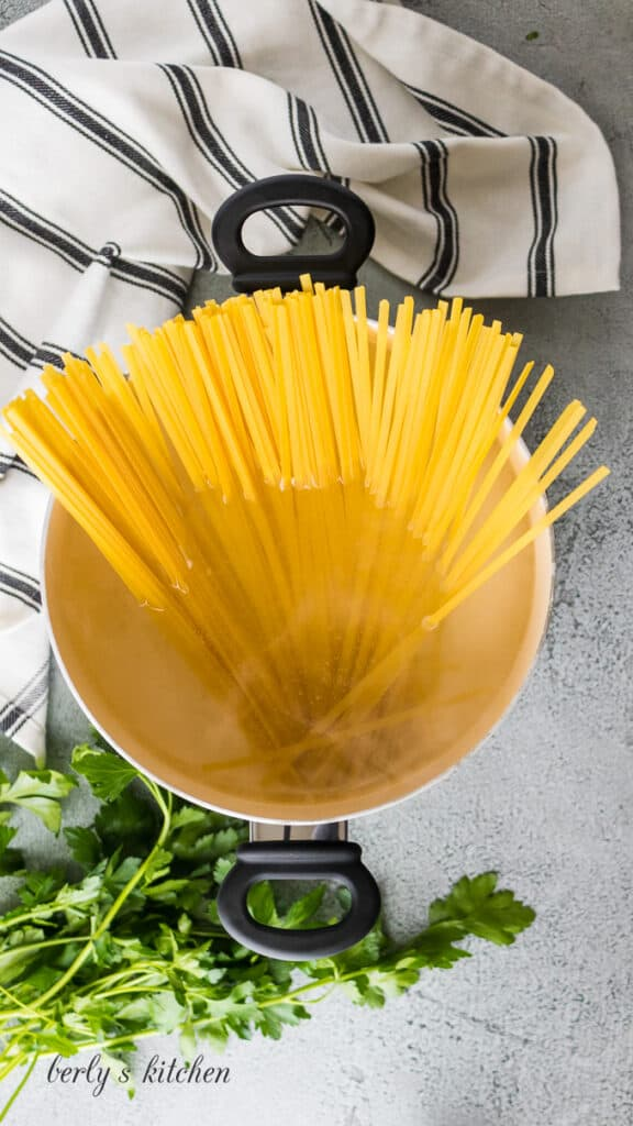 Fettuccine noodles cooking in a pan.