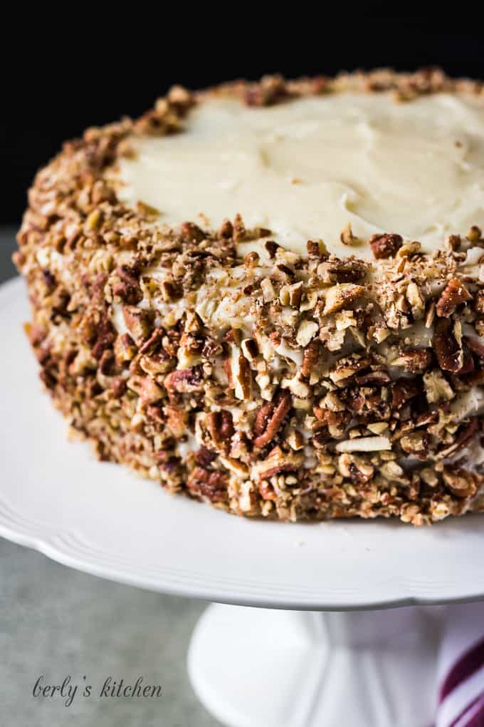 The whole moist carrot cake on a cake stand.