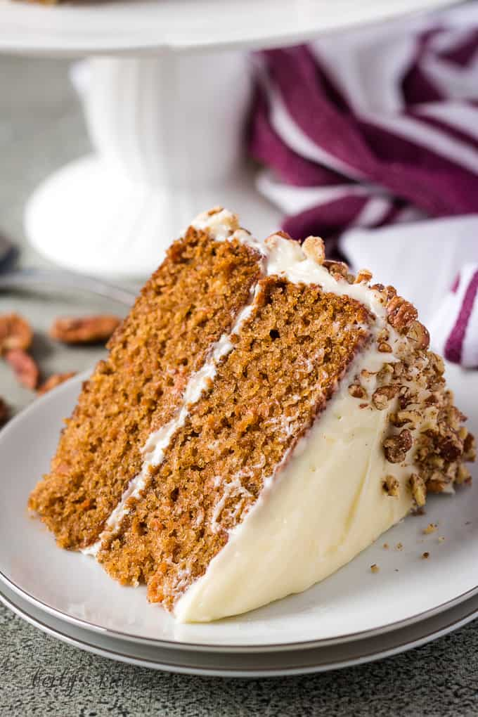 A piece of two layer carrot cake on a white plate.
