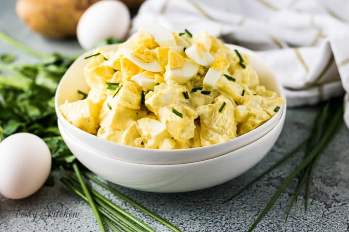 White bowl filled with potato salad next to eggs and chives.