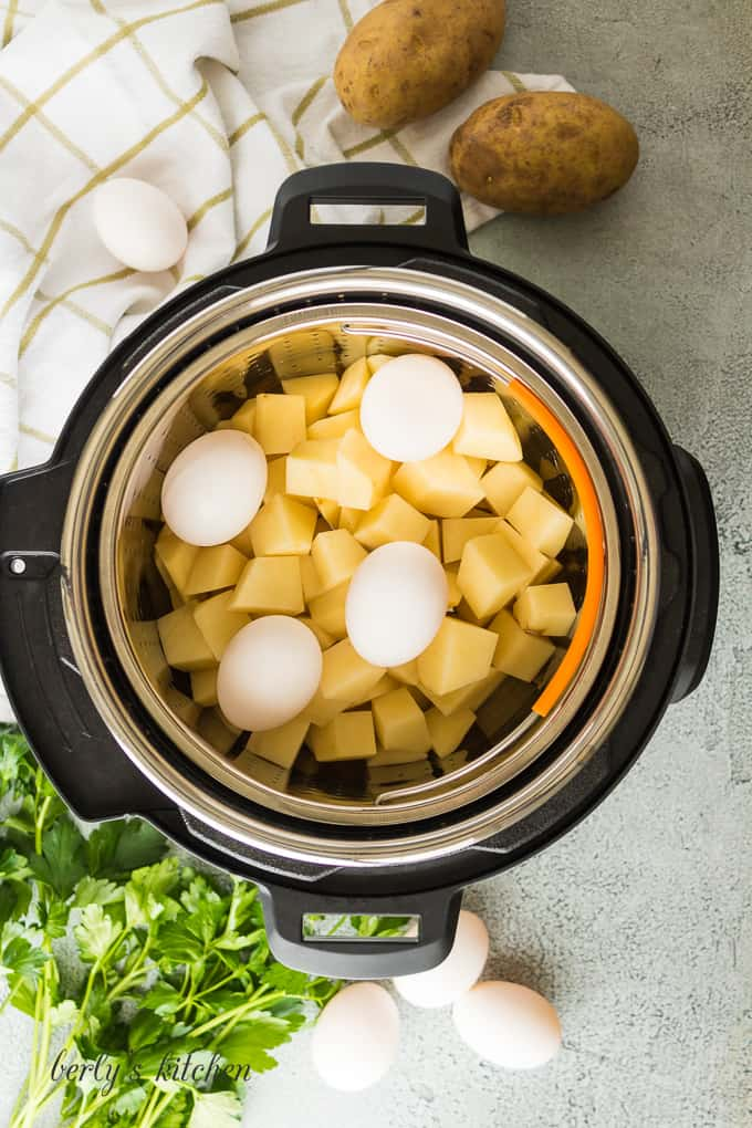 Ariel view of a pressure cooker with a basket of potatoes and 4 eggs on top.