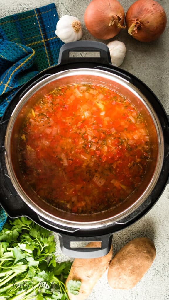 The soup has pressure cooked and is ready for more ingredients.