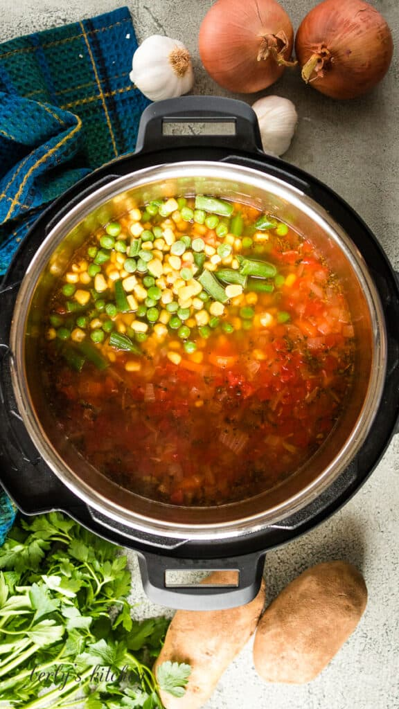 Frozen mixed vegetables being added to the hot soup.