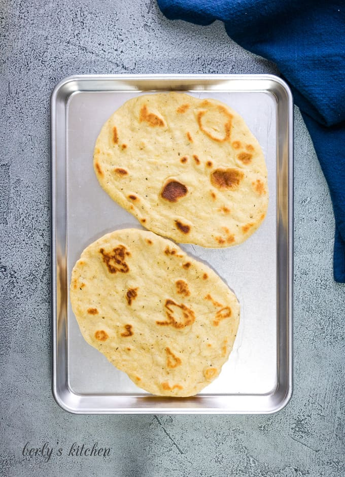 Two large flatbreads on a sheet pan.