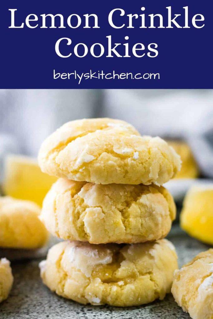 Three lemon crinkle cookies dusted with powdered sugar.