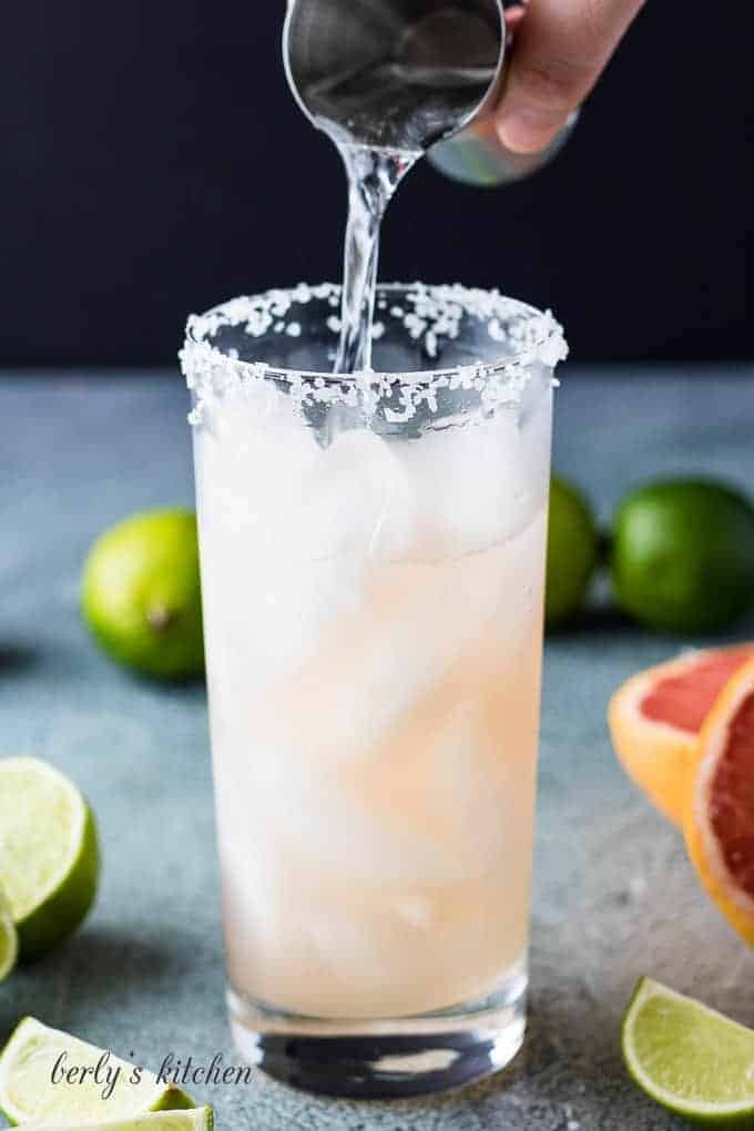Tequila being added to the grapefruit juice.
