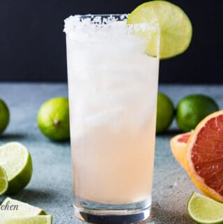 The paloma cocktail in a collins glass with a lime wedge.