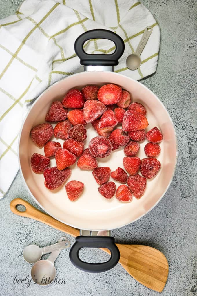 Whole fresh strawberries and sugar in a pot.