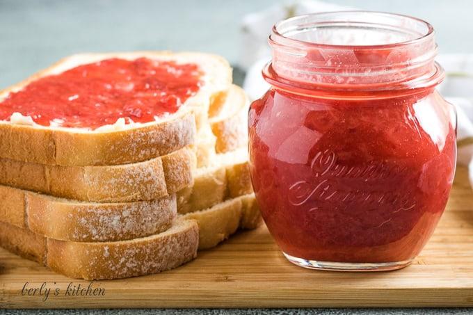 The finished strawberry jam on toast and a mason jar.