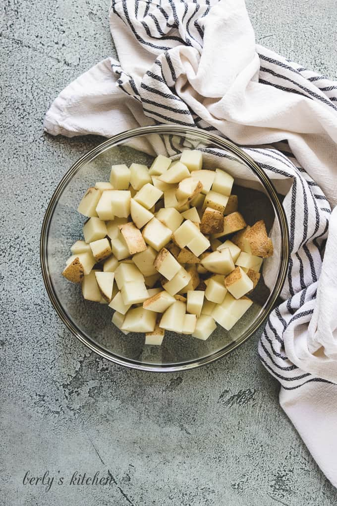 Cubed potatoes in a large glass mixing bowl.