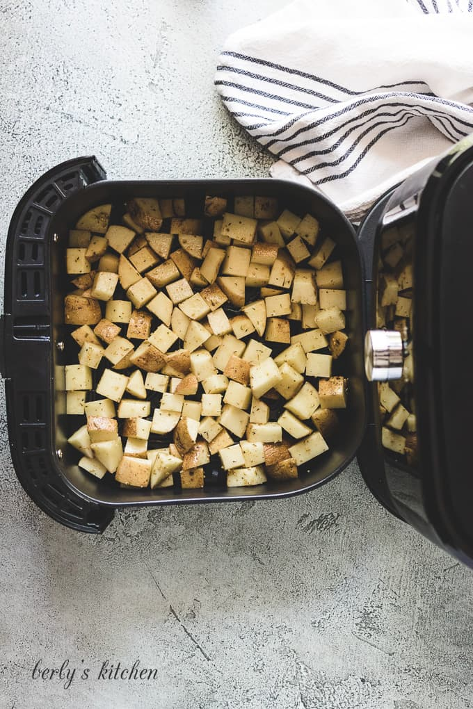 The potatoes have been transferred to the air fryer basket.