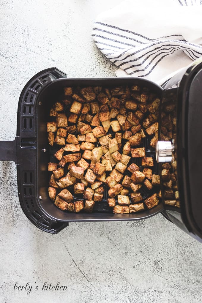 The home fries have cooked in the basket.
