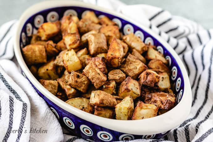 The seasoned air fryer home fries in an oval bowl.