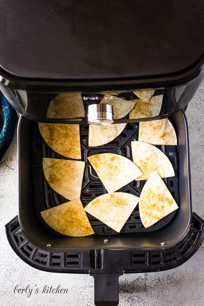 Corn tortilla chips cooking in an air fryer.