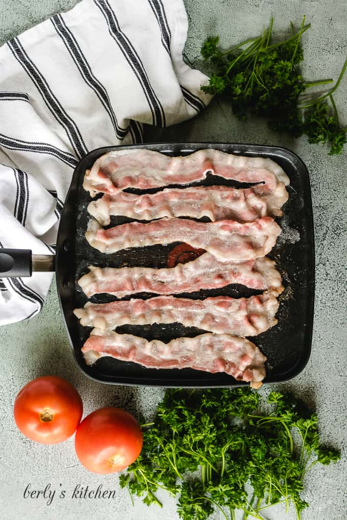 Six pieces of bacon being fried in a large skillet