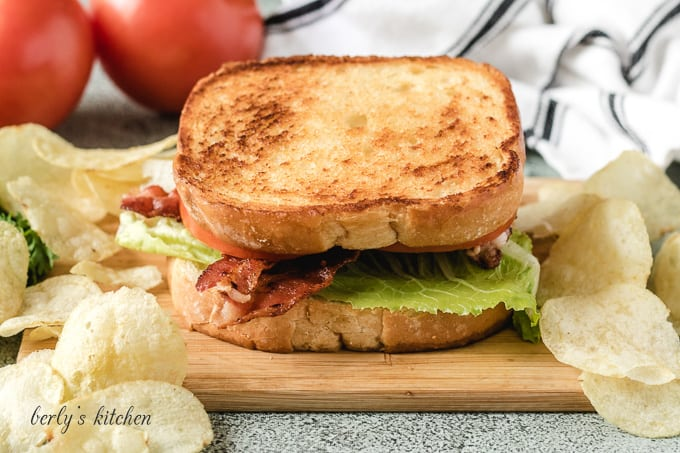 The blt sandwich on a cutting board with potato chips.