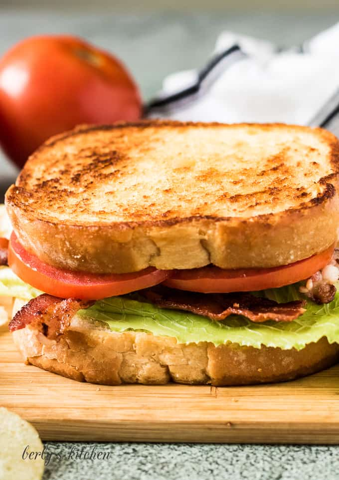 The completed BLT sandwich surrounded by potato chips.