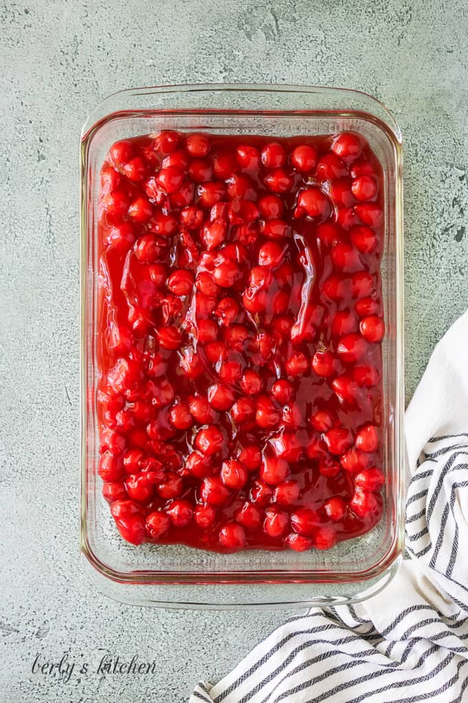 The cherry pie filling has been poured into the baking dish.