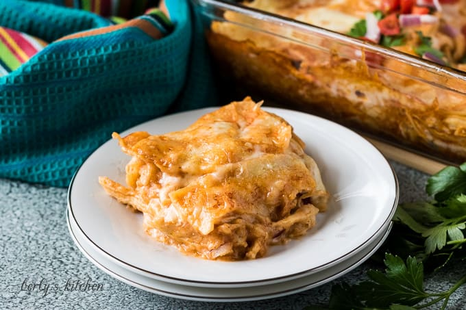 A piece of the cheesy layered chicken enchilada casserole on a plate.