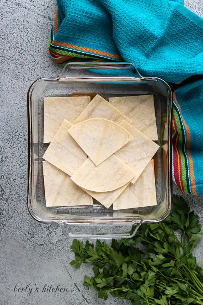 Corn tortillas cut into quarters are the second layer.