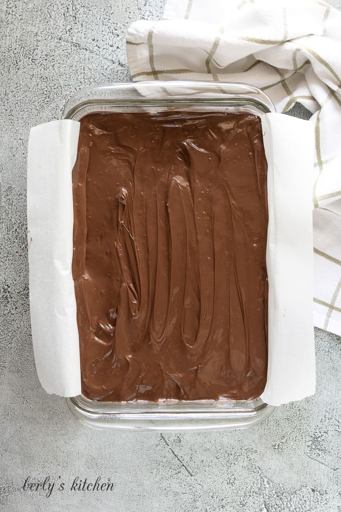 The chocolate topping has been poured over the filling.