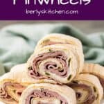 Multiple ham pinwheels stack on a square plate.