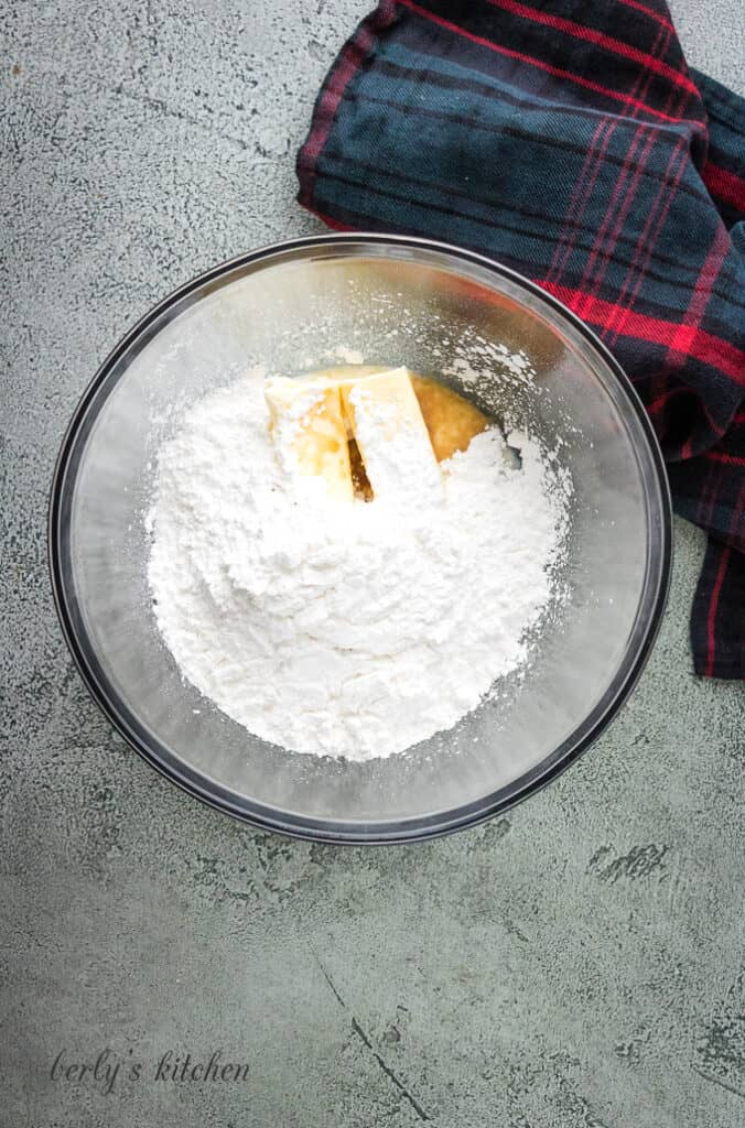 Butter, powdered sugar, and vanilla extract in a mixing bowl.
