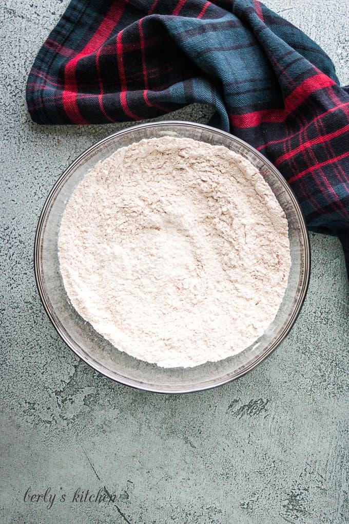 Flour, cinnamon, baking soda, and salt mixed in a bowl.