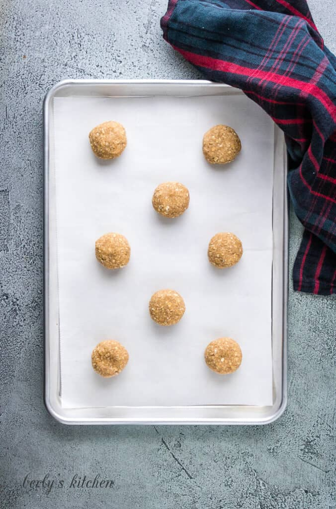 Eight balls of dough on a cookie sheet lined with parchment paper.