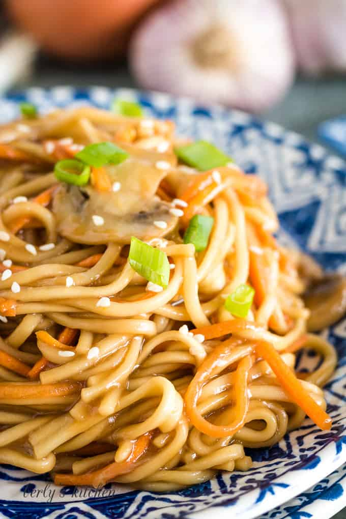Vegetable lo mein served on a plate and topped with sliced green onions.
